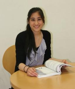 日本語の教科書を手に笑顔のカルメンさん