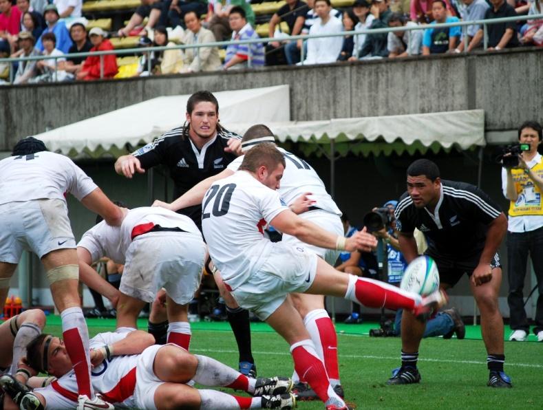 """U20ニュージーランド代表 vs. U20イングランド代表戦の後半、ハイパントを蹴るイングランドSHデーヴィッド・ルーイス(写真�央、背番号20)。今大会、イングランドは自らのスト�ングポイントを""""FW""""と定め、スクラム、(ラインアウト)モール、ラックからパントを蹴り、その繰り返しで徐々に相手ゴールに迫っていき、相手が焦れて反則を犯したらFBトーマス・ホーマーがペナルティゴールで〆る、というA代表にも通ずるシンプルかつリアリスティックな戦法を採用し、予選プールから相手チームを次々となぎ倒してきた。ニュージーランドとの決勝戦も、「成功事例から大きくかけ離れることはない」  (マーク・メープルトフト・イングランド代表監督、17日の準決勝・U20南アフリカ代表戦後のコメント)と、�攻法で相手に立ち向かっていったが、やはり王者の壁は厚かった【慶應塾生新聞会】"""