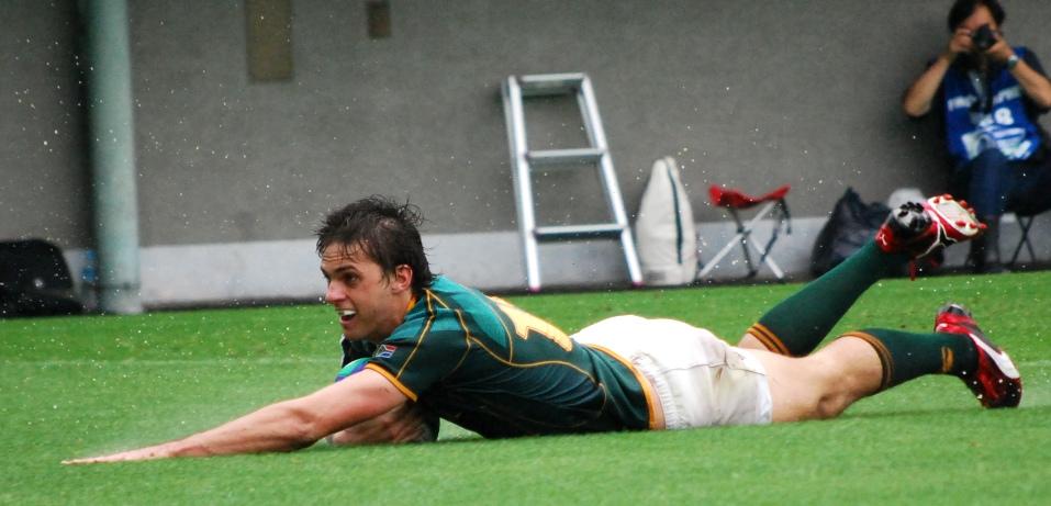 U20南アフリカ代表 vs. U20オーストラリア代表戦の後半、水飛沫を上げながらトライを決めるCTBニコラス・ハネコム。自陣20m付近で相手ラックからこぼれたボールを、南アフリカSH�ス・ク�ニエが拾い上げ、CTBニコラス・ハネコムに繋がり、最後は彼の独走トライで〆た。「イングランドに(準決勝で)敗れた後、チームを整えることが難しかった。決勝戦でなく3位決定戦であったため、気持ちを高めるのが難しいと予想していたが、うまくまとめることができた。選手を、そしてチームを誇りに思う」(CTB�ベルト・エベルソン・U20南アフリカ代表主将)。何より、オーストラリアにとってはモメンタムを掴みかけていた時間帯での失トライだっただけに、失望も大きかった【慶應塾生新聞会】
