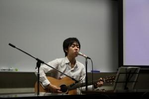 自作の曲をギターで弾き語りする山下さん