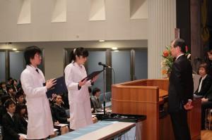 2人の学生代表が白衣を身に着け、学部長に意気込みを述べた(義塾広報室提供)