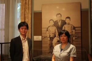 福澤先生の写真をバックに西澤教授と都倉講師