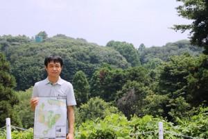 福山教授の後ろに広大な森がひろがる